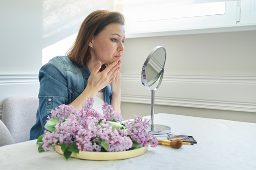 mature woman with make-up mirror massaging her face and neck